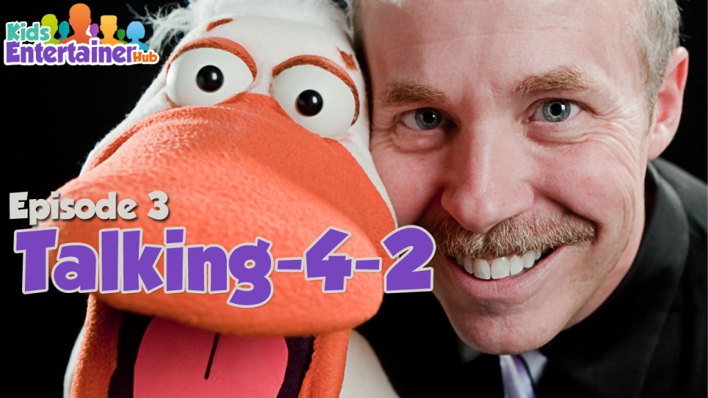 Tom Crowl is a Kids Entertainment Hub contributor. In the photo, he is smiling while holding a duck puppet with a large, orange bill right next to his face